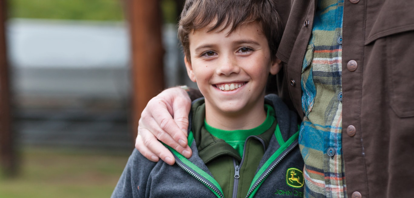 A young boy wearing a John Deere sweatershirt