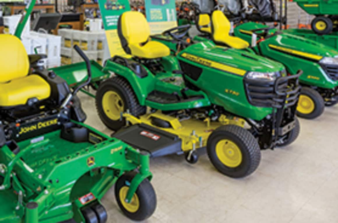 A line up of John Deere riding mowers on the dealership floor
