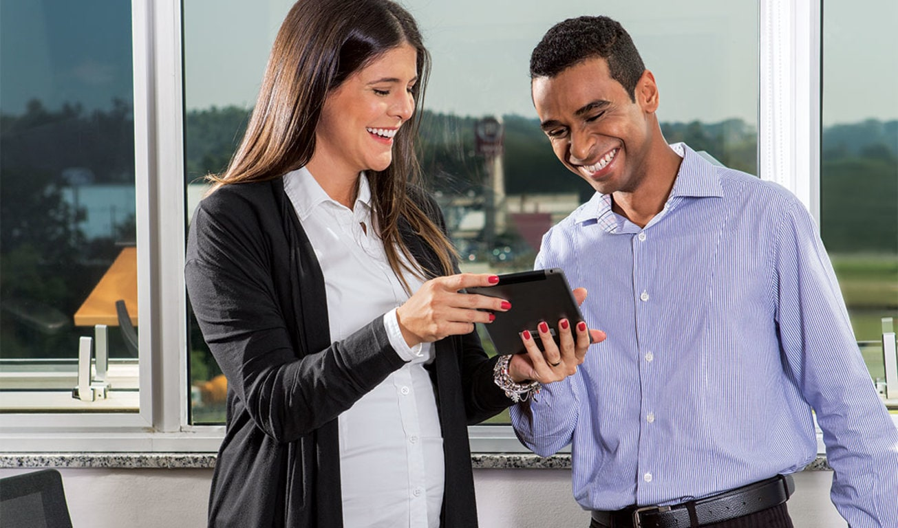 Man and woman look at tablet device