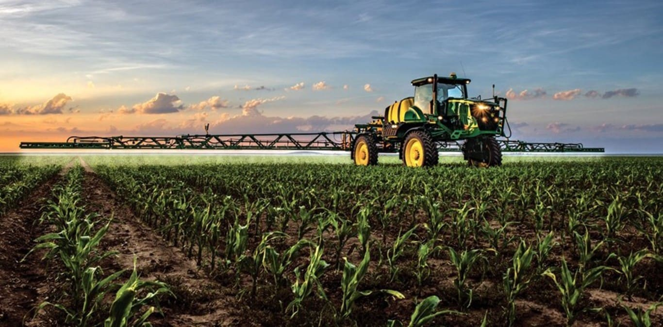John Deere sprayer working in a corn field with the sunset in the background