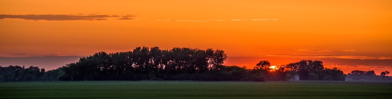 Farm at sunset with bright orange sky behind trees