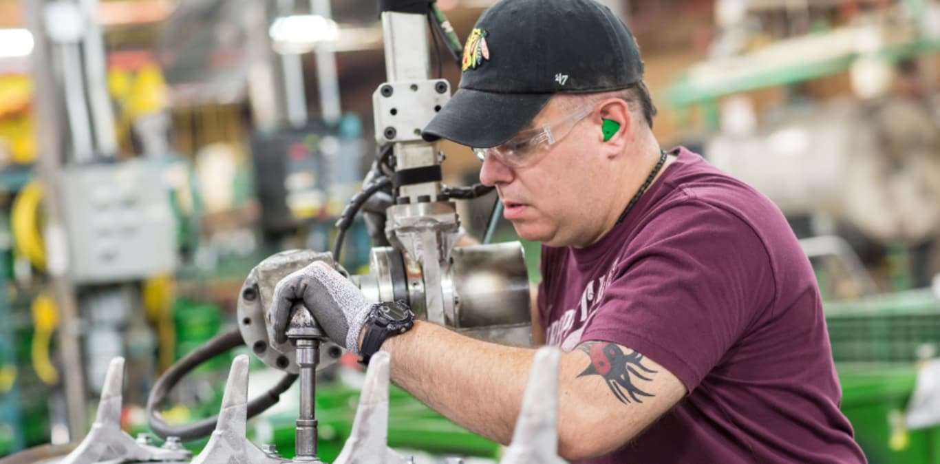 John Deere factory worker with safety glasses and hearing protection using a machine in the factory to build a piece of equipment
