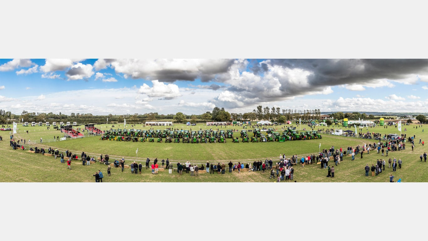 A panorama showing all 50 tractors and their drivers in the '100 Years of John Deere Tractors' display in the JD50 event's grand ring parade.