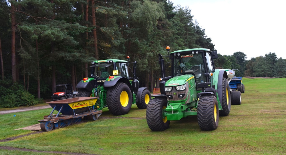 Two of MJ Abbott's new John Deere 6120M tractors topping up drain lines following drainage installation on a golf course reconstruction project.