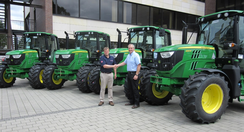 Adrian Abbott (left) of MJ Abbott Limited and Jamie Fisher of dealer R Hunt Ltd with the new John Deere 6120M tractor fleet at the handover in Mannheim.